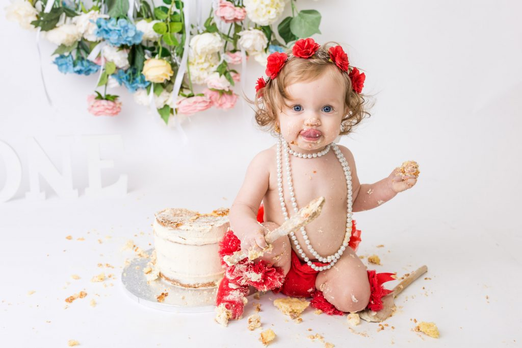 Little girl with red floral headband and pearl necklace eating cake