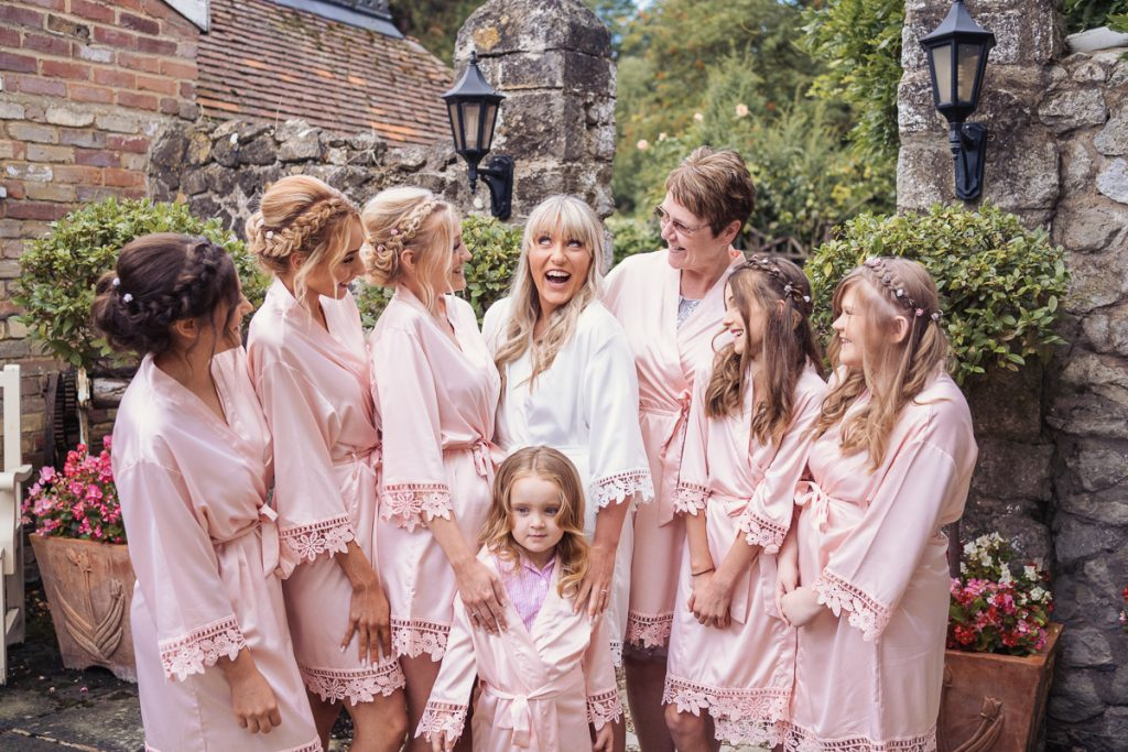 bride with her bridesmaids wearing robes