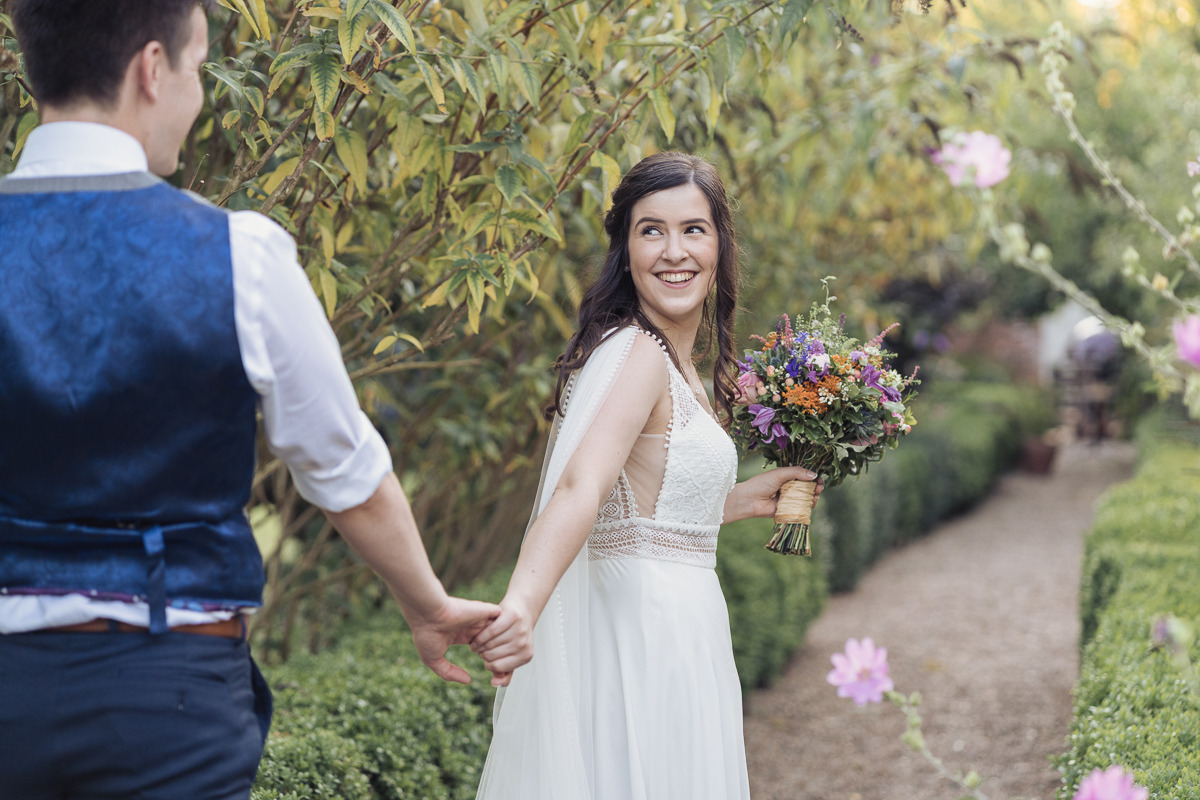 bride leading her husband down the path