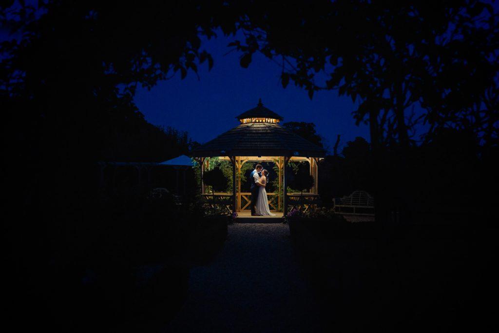 bride and groom under a gazibo