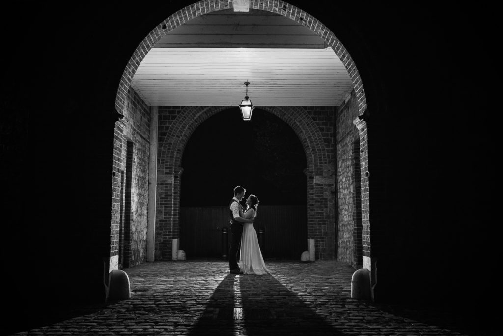 black and white photo of bride and groom under an archway