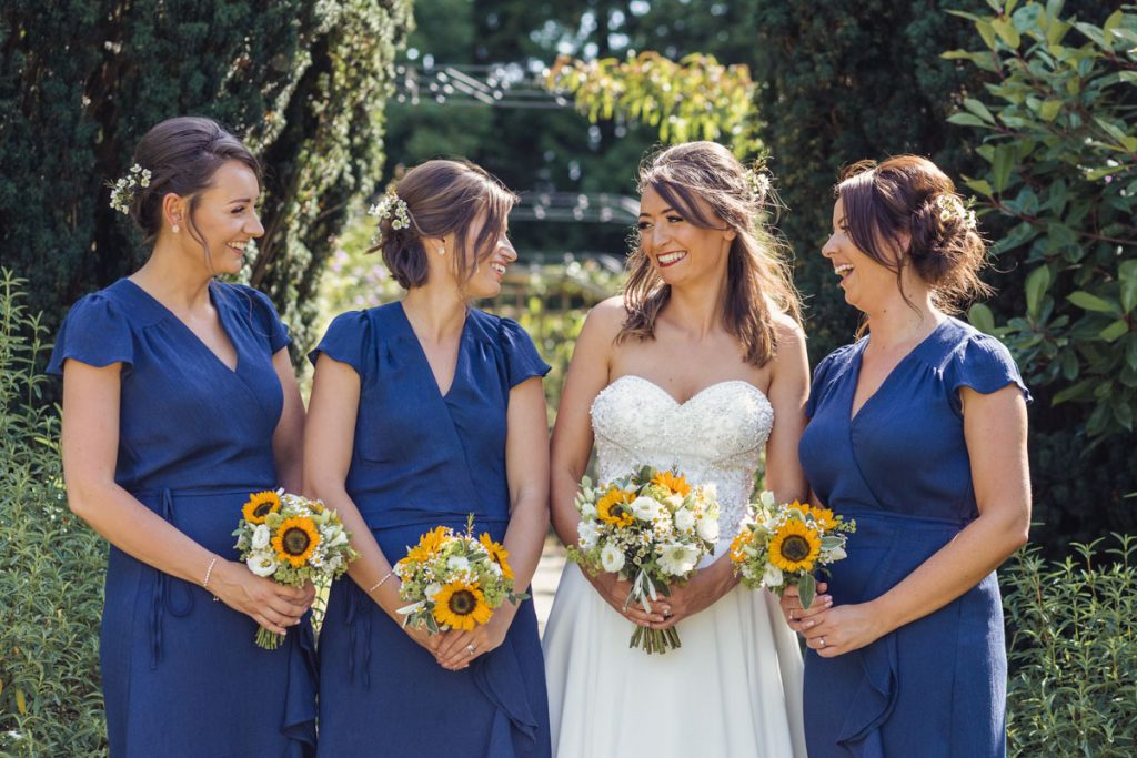 Bride and her bridesmaids all looking at one another while facing the camera
