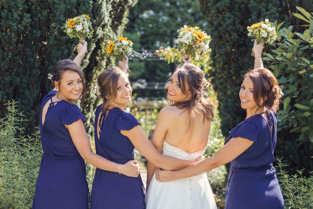 bride and her bridesmaid all holding a bouquet of flowers