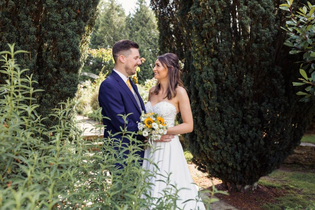 In the wild garden, a professional shot of the bride and groom looking at each other