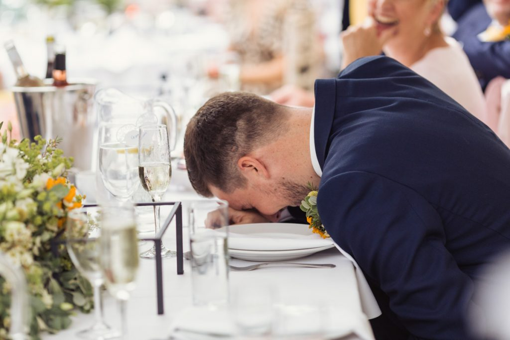 husband places head on dining table as he is laughing so much