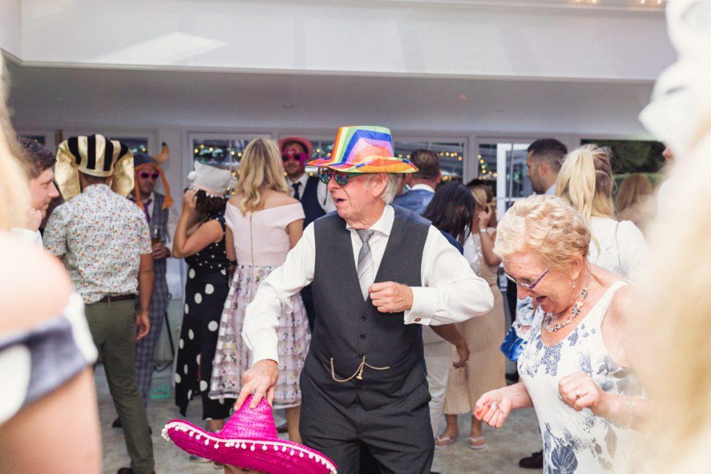 old man wearing fun hat dancing at a wedding