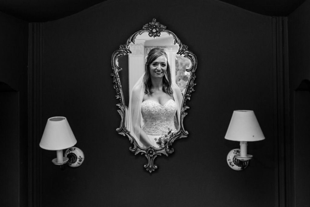 bride looking in mirror and her reflection showing