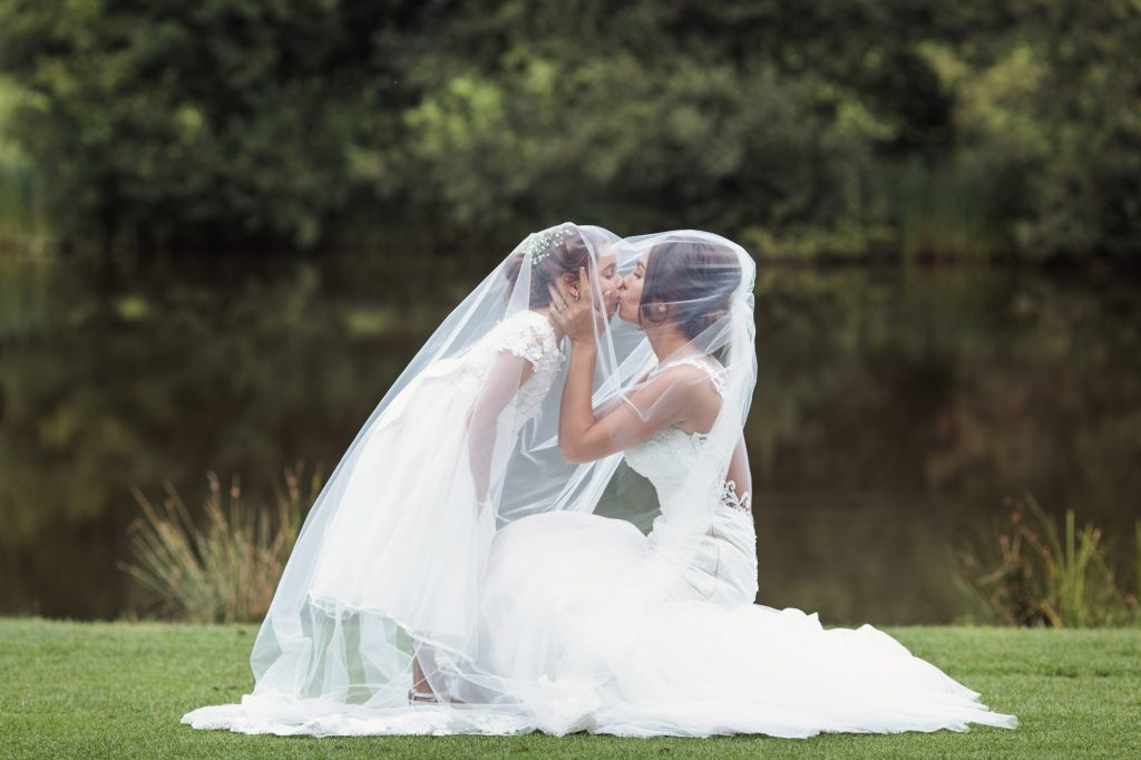 Mother gives her daughter a kiss under her white veil