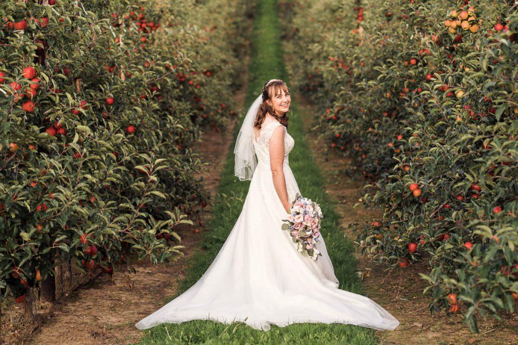 bride walking through an orange orchard