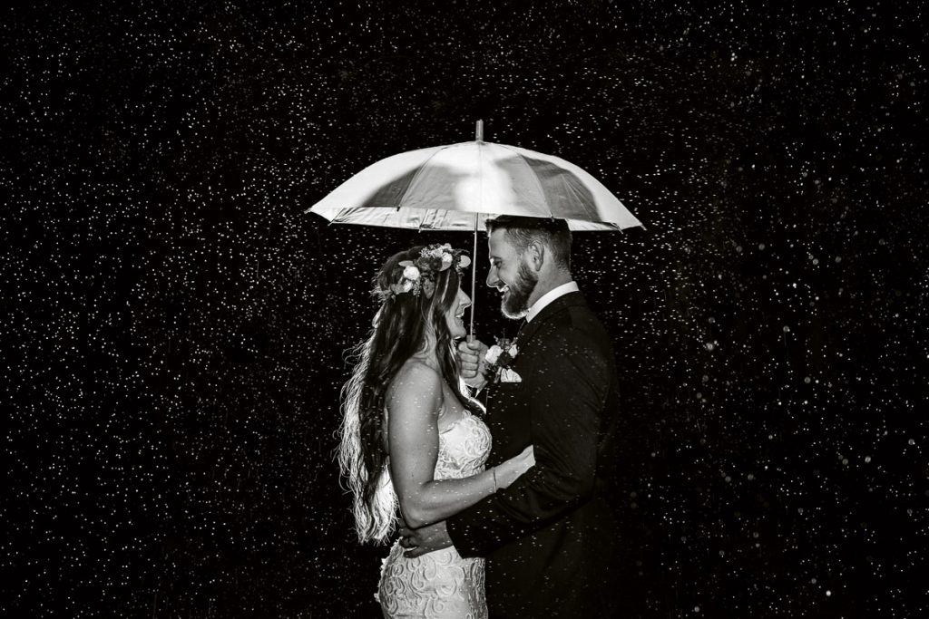 black and white photo of the wedding couple stood in the rain