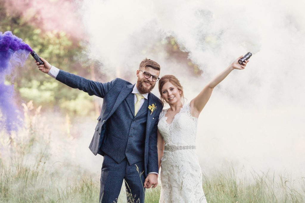 Holding colourful flares during a wedding photoshoot at Spa hotel