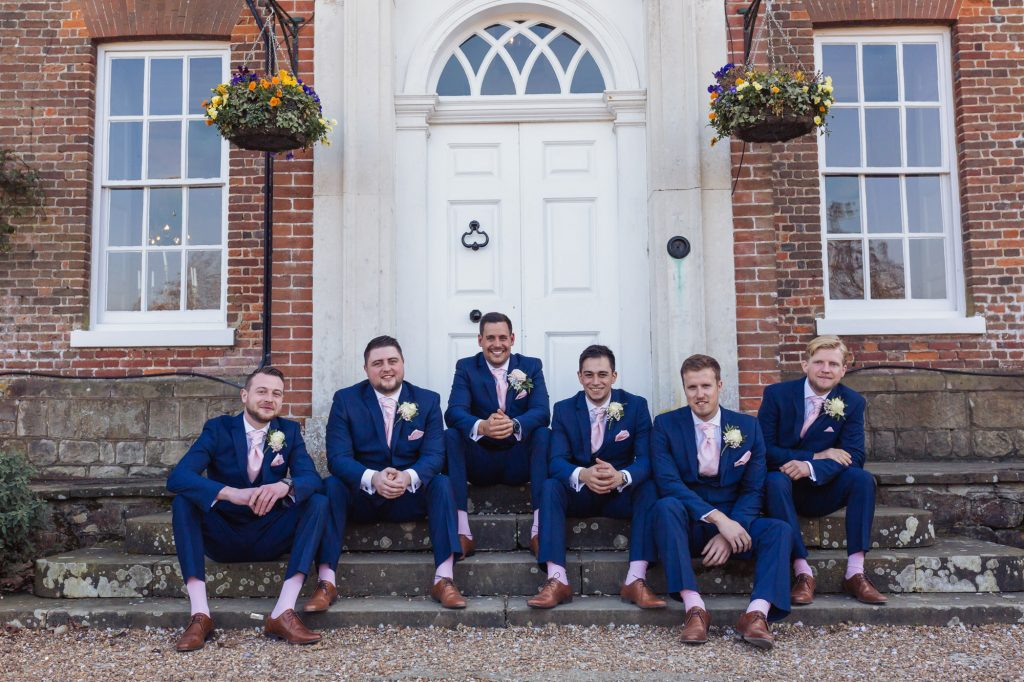 Chilston Park groom and his friends sat outside posing for a wedding photoshoot