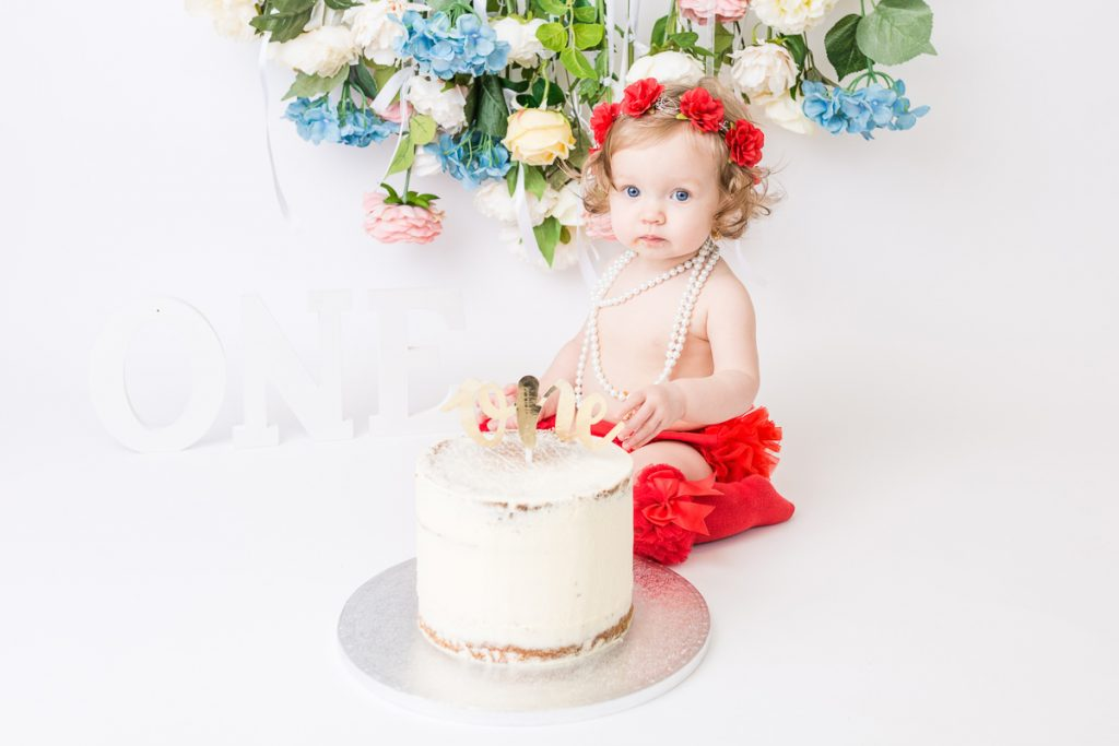 toddler sitting up eating cake