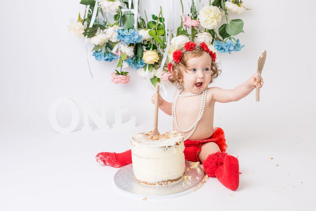 little birthday girl holding spoons