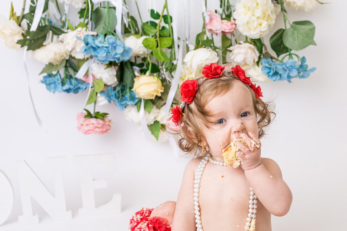 1st birthday girl eating cake