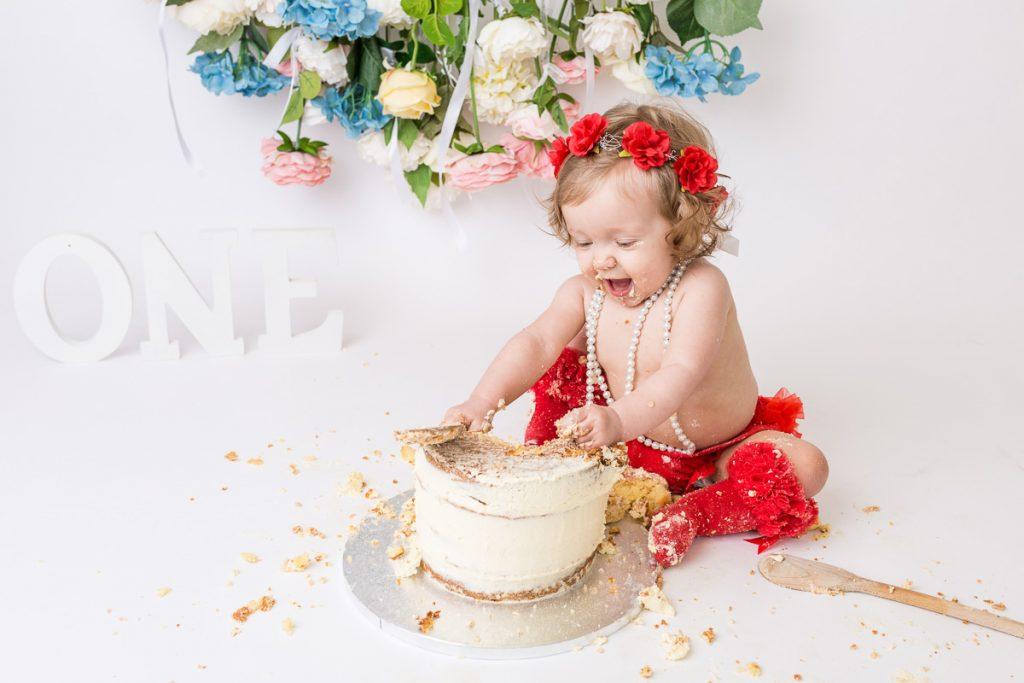 little girl 1st birthday smashing cake